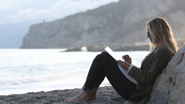 pull focus as woman looks at digital tablet, on pebble beach - solo una donna di età media video stock e b–roll
