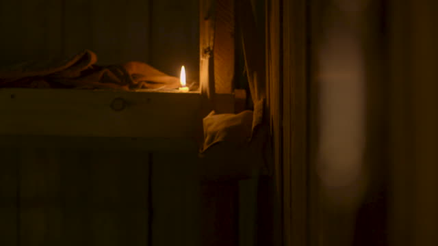 vídeos de stock, filmes e b-roll de pull focus between a hanging trench whistle and bunk beds illuminated by a candle in a wwi dugout, northern france. - bolsa tiracolo bolsa