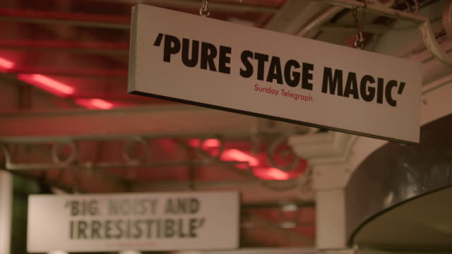 pull focus between a sign reading 'pure stage magic' sunday telegraph and 'big noisy and irresistible' sun herald australia hanging from the awning... - kritiker stock-videos und b-roll-filmmaterial