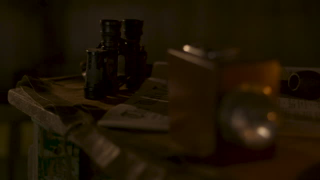 pull focus between a torch, binoculars and a newspaper in a wwi trench dugout, france. - world war one stock videos & royalty-free footage