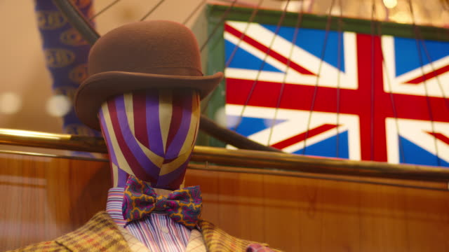 pull focus between an unusual striped mannequin in patterned garb and a union jack in a boutique shop window display in an arcade off jermyn street, piccadilly, uk. - hüten stock-videos und b-roll-filmmaterial