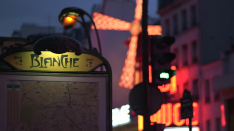 vidéos et rushes de pull focus between art-deco signage for blanche metro station and the windmill of the moulin rouge cabaret, pigalle, paris, france. - signalisation
