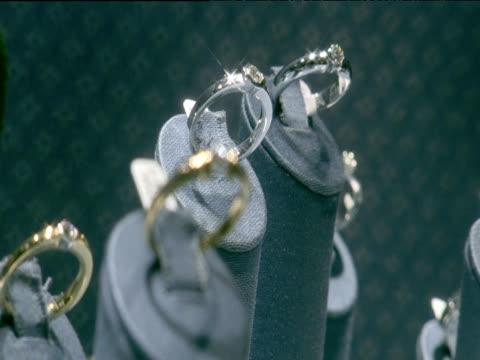 pull focus between diamond rings on display in jewellers - jewellery stock videos & royalty-free footage