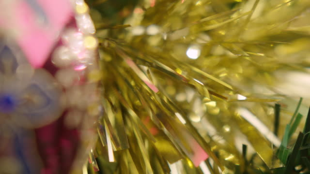 pull focus between festive gold tinsel and an ornate red bauble. - tinsel stock videos & royalty-free footage