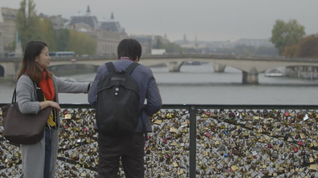 pull focus between 'love locks' chained to fencing on the pont des arts and the pont carrousel and beyond, paris, france, 2013. - eternity stock videos and b-roll footage