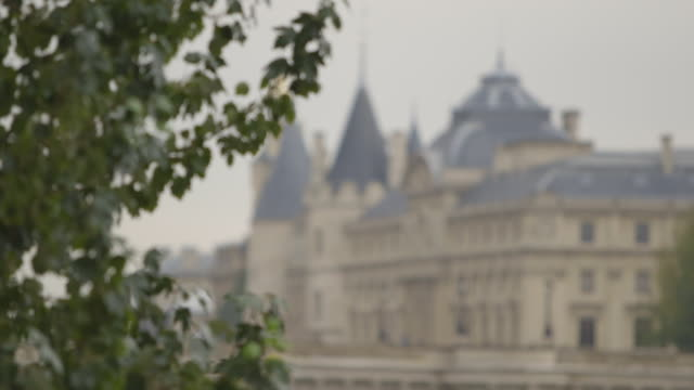 pull focus between the conciergerie and a tree, paris, france. - marie antoinette stock videos and b-roll footage