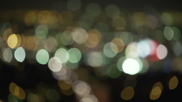 pull focus between two sizes of flickering bokeh created by the artificial lights of la at night, california, usa. - bbc stock videos and b-roll footage
