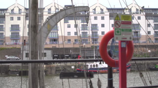 pull focus from a block of flats onto an orange lifebouy in bristol uk - life belt stock videos & royalty-free footage