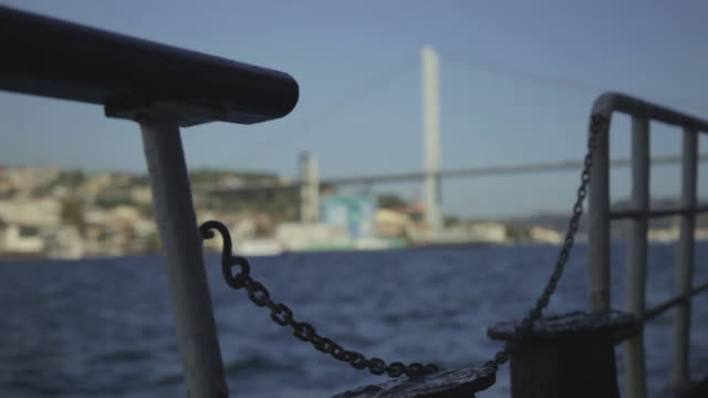 Pull focus from a boat to the Bosphorus Bridge in Istanbul.