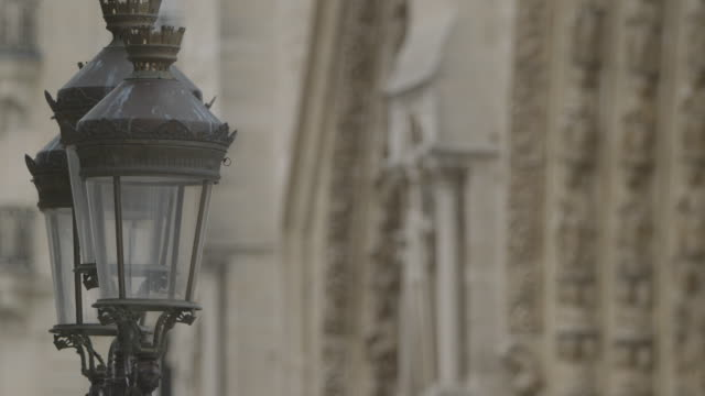 Pull focus from an ornate lamp post to figurines on the facade of Notre Dame de Paris, France.