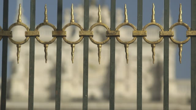 Pull focus from gilded railings to the clock face decorating the front of the Royal Palace of Madrid, Spain.