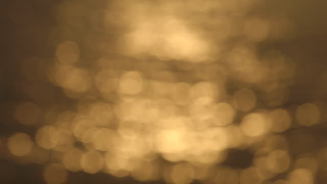 vidéos et rushes de pull focus from golden bokeh onto seawater - gold colored