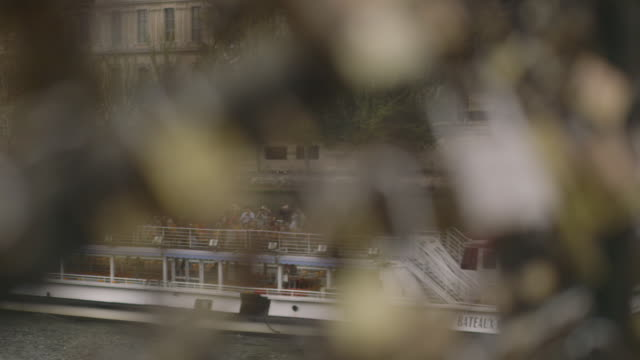 stockvideo's en b-roll-footage met pull focus from 'love locks' to a tour boat passing under the pont des arts, paris, france, 2013. - 2013
