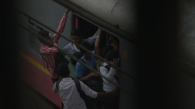 pull focus from men getting onto a male-only carriage of a busy train to overhead cables at wadala road station in mumbai, maharashtra, india. - rail transportation stock videos & royalty-free footage