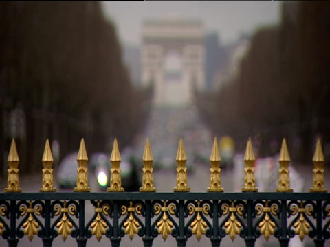 Pull focus from railings to Arc De Triomphe at distant end of busy Champs Elysees Paris