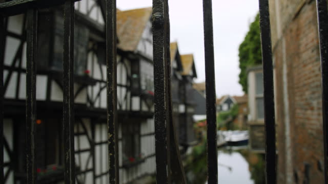 Pull focus from railings to Tudor houses overlooking the River Stour in Canterbury.