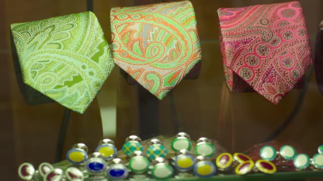 Pull focus from rolled neckties to cufflinks in a Jermyn Street shop window, London, UK.