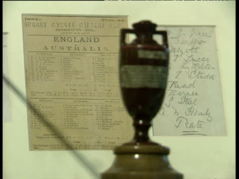 Pull focus from scorecard of 1882 Oval test match to original Ashes Trophy in MCC Museum at Lord's London