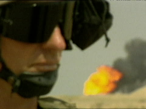 pull focus from soldier wearing goggles to oil fire burning in desert during iraq war 24 mar 03 - skibrille stock-videos und b-roll-filmmaterial