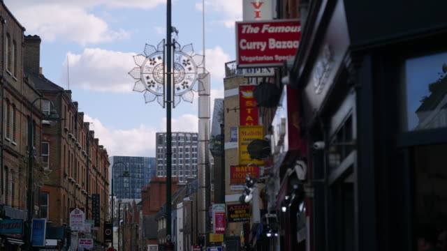 pull focus from the signs of curry restaurants to the brick lane jamme masjid, brick lane - mosque stock videos & royalty-free footage