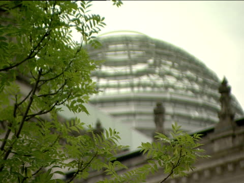 Pull focus from tree branches to new glass dome on roof of Reichstag Berlin