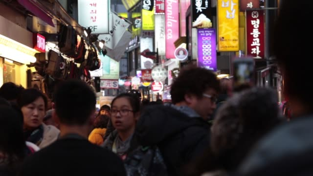 Pull focus into illuminated signage on buildings and heads of pedestrians in the Myeongdong shopping district in Seoul South Korea on Sunday Feb 15...