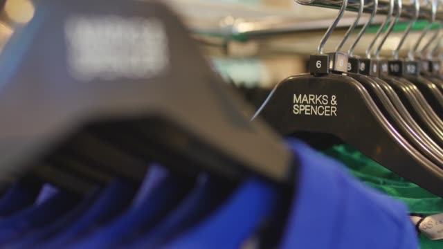 CS pull focus into Marks Spencer logo on black plastic hangers CS pull focus M S collection tag on treggings CS pull focus M S Collection tops CS...