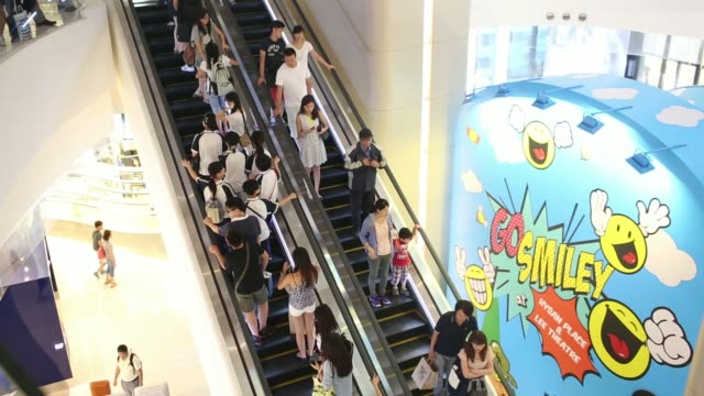 stockvideo's en b-roll-footage met pull focus into wide view of shoppers walking on and off escalators by the entrance inside the hysan development cos hysan place mall in the causeway... - hongkong eiland