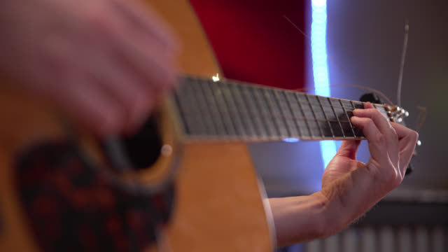 pull focus of an acoustic guitar being played - solo performance stock videos and b-roll footage