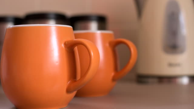pull focus of orange mugs in front of kettle - domestic kitchen点の映像素材/bロール