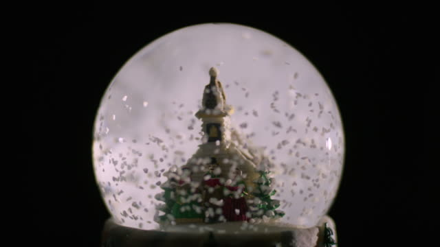 pull focus off a miniature plastic church and carol singers in victorian clothing surrounded by swirling 'snow' in a snow globe against a dark background. - victorian stock videos & royalty-free footage