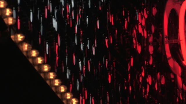 Pull focus off and onto large elliptical sequins next to lighting on the outside of a West End theatre, London, UK.