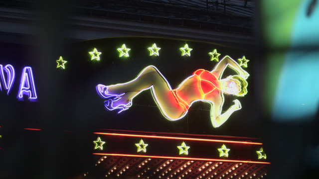 pull focus off bright neon lights of an adult establishment in the shape of a reclining, scantily-clad woman, pigalle, paris, france. - desire stock videos and b-roll footage