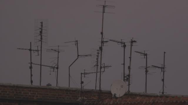 vídeos de stock, filmes e b-roll de pull focus off several aerials set at jaunty angles on a warsaw rooftop at dusk, poland. - onda radiofônica