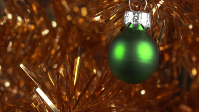 pull focus on a green bauble decorating a gold christmas tree. - tinsel stock videos & royalty-free footage