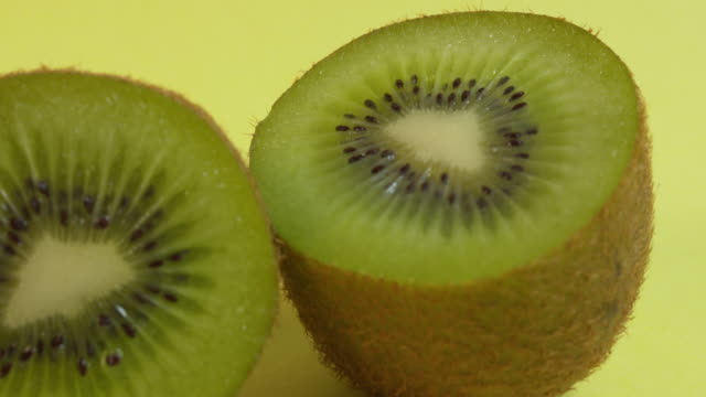 pull focus on a halved kiwi fruit against a plain yellow background. - ascorbic acid stock videos & royalty-free footage