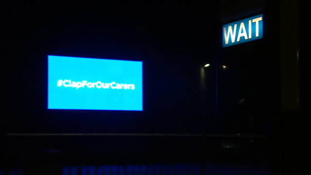 pull focus on billboard lit up blue advertising clap for our carers as the nation applauds the nhs for their work during the coronavirus - thank you englischer satz stock-videos und b-roll-filmmaterial