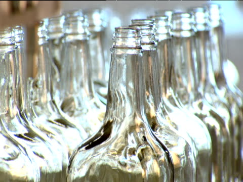 Pull focus on empty vodka bottles on production line in factory Moscow