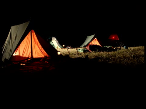 pull focus on illuminated tents in field at music festival - tent stock videos and b-roll footage