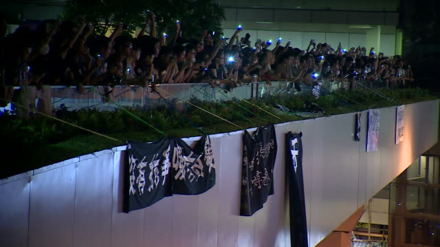 pull focus on lit up phones of pro-democracy demonstrators at night. a large cardboard cut out of cy leung's head is carried through the crowd - politische wahl stock-videos und b-roll-filmmaterial