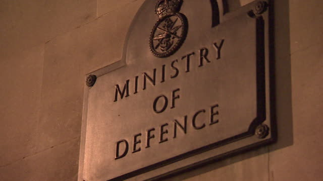 stockvideo's en b-roll-footage met pull focus on ministry of defence sign at whitehall headquarters at night - ministerie van defensie