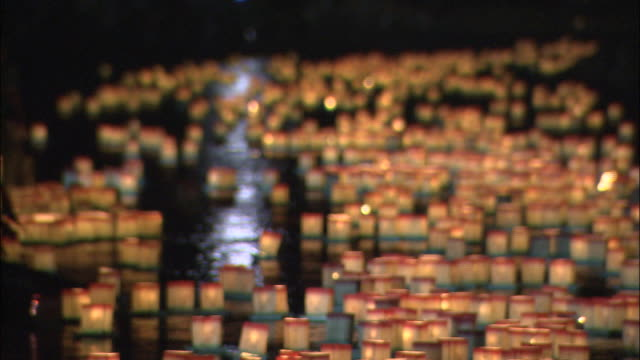 pull focus on paper lanterns floating down river (eiheiji lantern launching rite - way of seeing off dead spirits held during bon festival), fukui - lantern stock videos & royalty-free footage