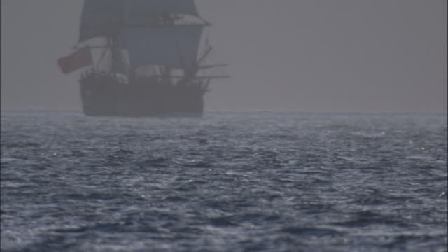 Pull focus on replica of HMS Endeavour under full sail.