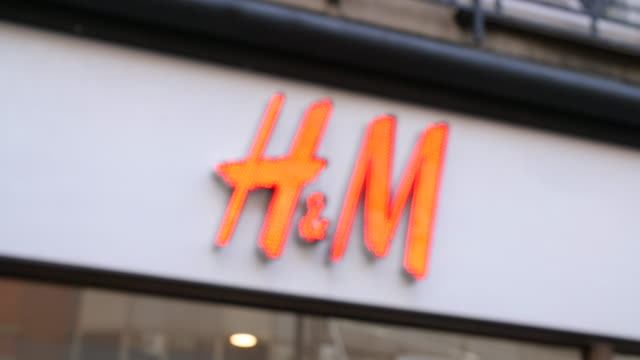 pull focus on the illuminated h&m shop sign on london's oxford street. - shop sign stock videos & royalty-free footage