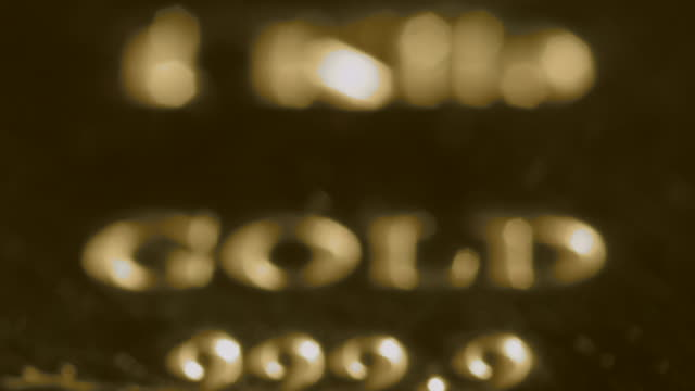 pull focus on the lettering and numbers stamped onto a bar of gold. - 焦点点の映像素材/bロール
