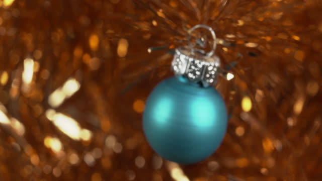 pull focus onto a blue christmas bauble hanging from a gold tinsel tree. - tinsel stock videos & royalty-free footage