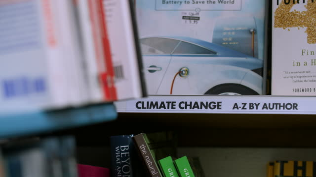 Pull focus onto a 'Climate Change' sign on a bookshelf