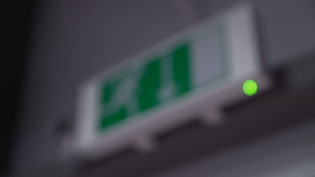pull focus onto a fire exit sign suspended above a doorway - exit sign stock videos & royalty-free footage