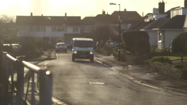 pull focus onto a milk float driving along a residential street. - morning stock videos & royalty-free footage