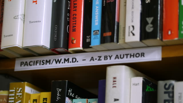 Pull focus onto a 'Pacifism' sign on a bookshelf